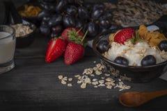 Yoghurtblandninghavremjölet, jordgubben och druvatoppning i svart bunke på trätabellen med skeden, druvor, jordgubbe, mjölkar i e arkivfoto