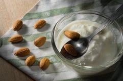 Yoghurten med mandlar kärnar ur på tabelltorkduken arkivfoto
