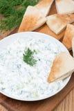 Yoghurtsåstzatziki med örter, gurka och vitlök och pitabröd Arkivfoto