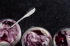 Yoghurts met vruchten assortiment in glaskommen op donkere marmeren achtergrond Gezonde natuurlijk en fruit, gastronomisch dieet, stock afbeelding