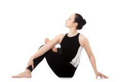 Yogi athlete girl in yoga asana parivritta Eka Pada Agnistambhas Stock Photography
