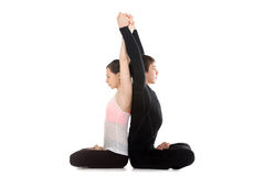 Yogi couple doing exercises for spine and shoulders in lotus pos Stock Photography