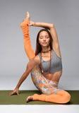 Yogi die op mat zitten Stock Foto's