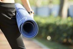 Yogi féminin avec le tapis de forme physique photo stock