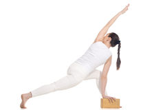 Yogi female exercising with wood brick Stock Image
