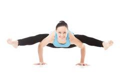 Yogi female in yoga Tittibhasana, Insect Pose. Smiling sporty yogi girl doing fitness exercises, handstand, yoga asana Tittibhasana, arm balance Firefly posture stock image