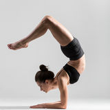 Yogi girl performs asana pincha mayurasana Royalty Free Stock Photography