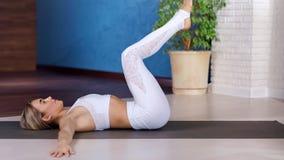 Yogi jong vrouw het ontspannen het praktizeren yoga opheffend been van één kant aan een andere die op mat liggen stock video