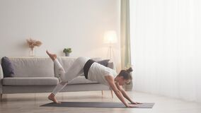 Active flexible woman practicing yoga stretching at home, practicing pilates, raising her leg up, slow motion
