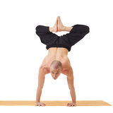 Yogi looking at camera while doing handstand Stock Photography