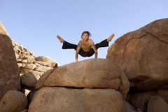 Yogi On The Rocks. Free spirited man practicing hatha yoga posture titibasana on some giant rocks Royalty Free Stock Image