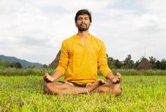Yogi sitting in lotus pose. Indian man yogi in lotus pose resting hands on knees sitting in grass as natural background stock image