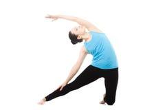 Yogi som är kvinnlig i yogaasanaen Parighasana Royaltyfri Fotografi