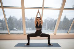 Yogi woman in a dark jumpsuit practicing yoga concept, standing in Sumo Squat exercise, Goddess pose, working out, Stock Images
