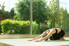 Yogi woman does yoga exercises, working out, practicing pranayama breathing technique. Spacious room with big full length windows. royalty free stock photos