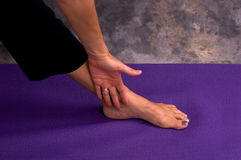 Yogic hand and foot. The back of a woman's hand rests on her ankle while doing variation of triangle pose, close up of hand and foot on purple mat Royalty Free Stock Photo