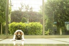 Yogikvinnan gör yogaövningar och att utarbeta, den praktiserande pranayamaandningtekniken Rymligt rum med stora fulla längdfönste arkivbilder