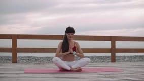 Yogikvinnan sitter i lotusblommaposition på havskusten som mediterar lager videofilmer