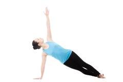 Yogin som är kvinnlig i yogasidoplanka, poserar Royaltyfri Foto
