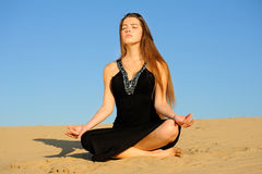 Yogini girl. Girl in black dress sitting in a lotus position on the sand Stock Photo