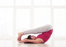 Yogini mince se trouvant sur le dos sur le tapis dans des jambes d'une position de yoga Images stock
