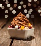 Yogourt glacé de Brown au-dessus des fruits coupés en tranches sur la cuvette Image stock