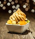Yogourt glacé jaune sur des tranches de fruit sur la cuvette blanche Photos stock