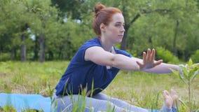 Yogui de la mujer que practica al aire libre el estirar de los tendones de la corva, profesor hermoso de la yoga almacen de video