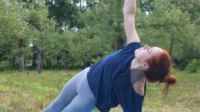 Yogui femenina que hace yoga en el asana de la balanza del parque, práctica en vida sana del aire fresco almacen de metraje de vídeo