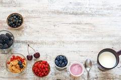 Yogur, bayas frescas, copos de maíz y taza de leche en una tabla de madera Fotografía de archivo libre de regalías