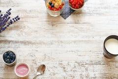 Yogur, bayas y taza de leche en una tabla de madera Fotos de archivo