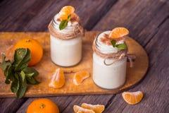 Yogur blanco natural del organig fresco en los tarros de cristal con la mandarina Imagenes de archivo