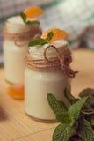 Yogur blanco natural del organig fresco en los tarros de cristal con la mandarina Foto de archivo libre de regalías