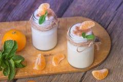 Yogur blanco natural del organig fresco en los tarros de cristal con la mandarina Foto de archivo