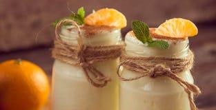 Yogur blanco natural del organig fresco en los tarros de cristal con la mandarina Fotos de archivo libres de regalías