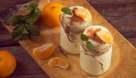 Yogur blanco natural orgánico fresco en los tarros de cristal con la mandarina Fotos de archivo libres de regalías