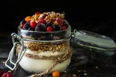 Yogur con el granola y las bayas en pequeño tarro, fresas, arándanos , grosella negra dulzor Yogur hecho en casa Alimento sano imagen de archivo libre de regalías