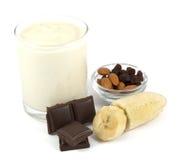 Yogur con el plátano, el chocolate, las almendras y las pasas Foto de archivo