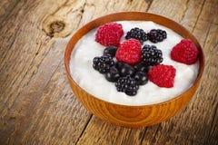 Yogur con las bayas del bosque en cuenco de madera Foto de archivo