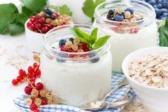 Yogur con las bayas y las comidas de desayuno frescas en la tabla Fotos de archivo