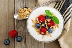 Yogur con las frambuesas, arándanos, granola, escena de arriba en la madera rústica Foto de archivo libre de regalías