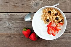 Yogur con las fresas y el granola sobre la madera rústica Foto de archivo