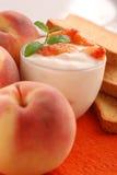 Yogur con sabor del melocotón imagenes de archivo