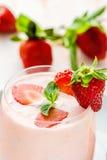 Yogur de la fresa en un vidrio con las rebanadas de bayas frescas, de hojas de menta y de fresas maduras Imagen de archivo