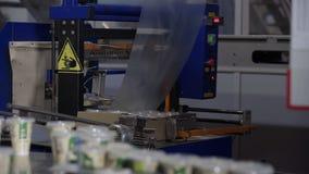 Yogur embalado en envases de plástico en cadena de producción Línea de envasado en la fábrica de la lechería metrajes