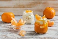 Yogur en pequeños tarros con las rebanadas del mandarín en una tabla blanca de madera imagen de archivo