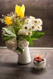 Yogur griego con las semillas del chia del coco y las frutas frescas al lado de las flores en el florero Fotografía de archivo