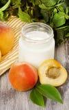 Yogur hecho en casa con el albaricoque fresco en la tabla de madera Foto de archivo