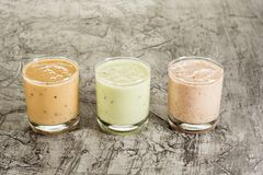 Yogur hecho en casa fresco tres en un vidrio con el ciruelo, el kiwi y el higo En un fondo concreto con el espacio de la copia fotos de archivo