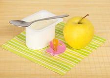 Yogur, manzana y pacificador Imagenes de archivo